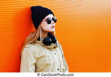 hübsch, blond, tragen, a, schwarzer hut, und, kopfhörer, hört, zu, musik, genießt, freiheit, kühl, hüfthose, m�dchen, stadt, gegen, a, bunte, wand, straße mode, begriff, städtisch, stil
