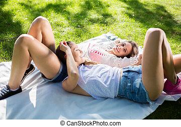 hübsch, glücklich, weibliche , friends, liegen, auf, decke, park