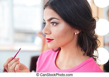 hübsch, junge frau, setzen, roter lippenstift