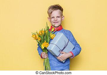 hübsch, junge, halten blume, bündel, und, geschenk, box., valentines, day., birthday., mutter, day., studio, porträt, aus, gelber hintergrund
