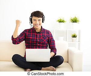 hübsch, junger mann, laptop benutzend, edv, mit, kopfhörer