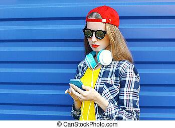 hübsch, kühl, m�dchen, hört, zu, musik, in, kopfhörer, und, gebrauchend, smartphone, aus, blauer hintergrund