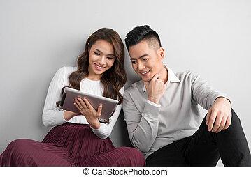 hübsch, lächeln, asiatisches, liebe, zusammen, sitzen boden, genießen, gebrauchend, digital tablette
