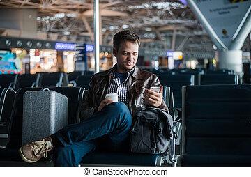hübsch, lächelnden mann, in, ungezwungener verschleiß, besitz, gepäck, und, messaging, durch, seine, handy, während, sitzen, an, der, halle, von, flughafen, mit, kaffeetasse