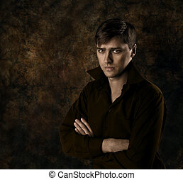 hübsch, mann sitzen, aus, dunkel, brauner, gotische , hintergrund, mit, gekreuzt, hands., ernsthaft, anschauen, kamera.