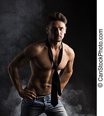 hübsch, shirtless, muskulös, mann stehen, auf, dunkler hintergrund