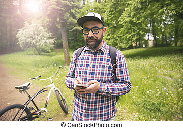 hüfthose, mann, an, park, mit, fahrrad, gut bewegliches telephon