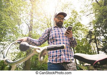 hüfthose, mann, besitz, fahrrad, gebrauchend, smartphone, draußen