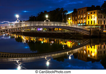 Night view of famous illuminated Ha Penny Bridge in Dublin, Ireland with reflection in the river