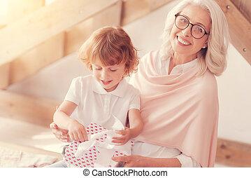 haar, cadeau, opening, kleinzoon, terwijl, fototoestel, oma, het glimlachen, blij