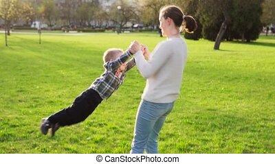 haar, lente, houden, park, armen, zoon, ondergaande zon , moeder, whirls, hem