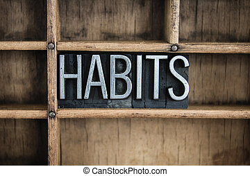 "The word ""HABITS"" written in vintage metal letterpress type in a wooden drawer with dividers."
