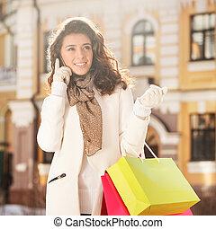 hablar, con, friend., hermoso, mujeres jóvenes, hablar, en, el, teléfono móvil, y, tenencia, el, bolsas de compras