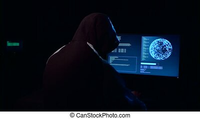 Hacker in a large dark room at the table enters the virus data into the computer