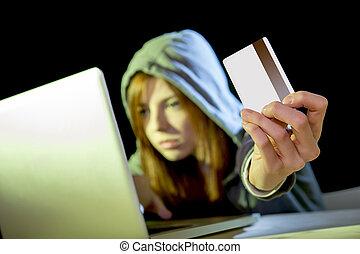 hacker girl holding credit card violating privacy holding credit card in cybercrime and cyber crime
