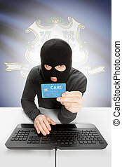 Hacker holding credit card with US state flag on background - Connecticut