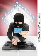 Hacker holding credit card with US state flag on background - Arkansas