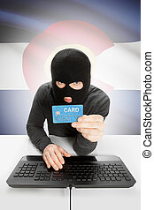 Hacker holding credit card with US state flag on background - Colorado