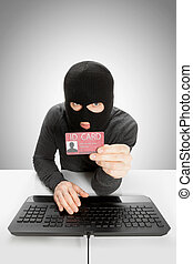 Hacker holding ID card in hand - Hacker with ID card in hand