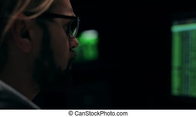 Thoughtful male hacker in eyeglasses looking at running lines on monitors, closeup