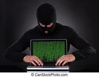 Hacker stealing data of a laptop computer - Hacker in a ...