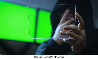 Hacker using clear tablet with green screen monitor...
