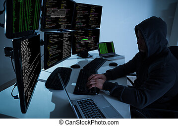Hacker Using Computers To Steal Data - Rear view of hacker...