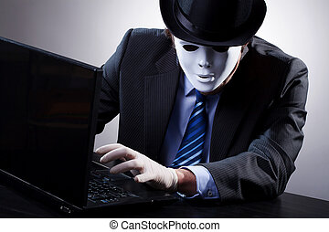 Hacker wearing a suit and mask in front of computer