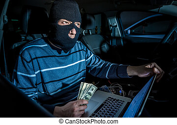 Hacker with a laptop inside a car