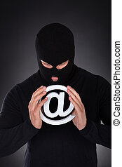 Hacker with an internet domain symbol - Hacker dressed in...
