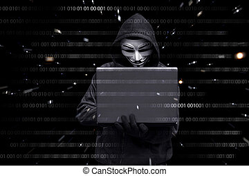 Hacker with vendetta mask typing on a laptop