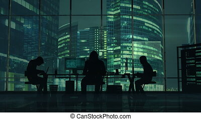 Hackers at work on the background of green office buildings
