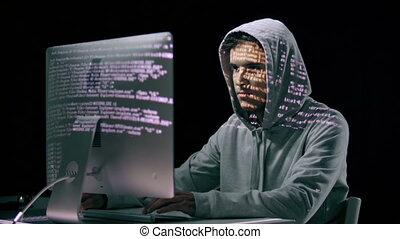 Hacking It - Hacker in hoodie computing with projections on...