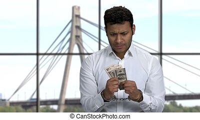 Hadcuffed businessman holding hundred dollars. Cables and tower of the suspension bridge on the background. Corruption concept.
