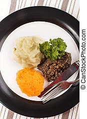 haggis with mashed potato, turnip and parsley on a plate -...
