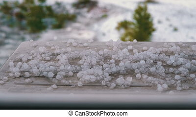 Hail Outside the Window. Pieces of hail lie on the windowsill behind a plastic window. Natural phenomenon, hailstones bounce off the windowsill, there is a cold rain with hail. Bad weather.