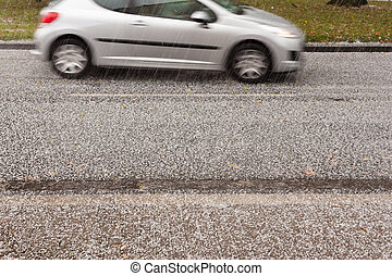Hail Storm on the Road - Small car driving on road through...