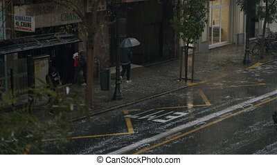 VALENCIA, SPAIN - NOVEMBER 27, 2020: A window shot of a town street with cars and passers-by, rushing away from the hailstorm