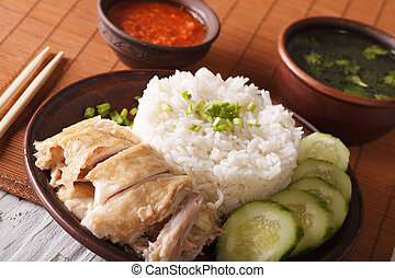 Hainanese chicken rice with cucumber closeup on a plate. ...
