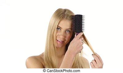 Hair. Beautiful Blond Brushing Her Hair. Hair Care. slow...