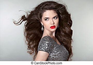 Hair. Beautiful Brunette Girl. Healthy Long Hair. Red lips. Fashion earrings jewels. Beauty Model Woman. Blowing Hairstyle.