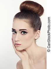 Portrait of young beautiful slim girl with cat eyes make-up and hair bun