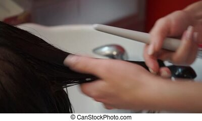 Hair care in the beauty salon - The master hairdresser uses...