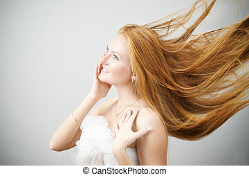 Hair Care - Portrait of a beautiful young woman on a gray...