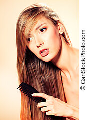 hair care - Young pretty blonde woman combing her beautiful...