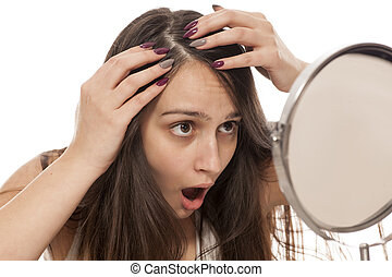 hair check - young shocked woman looks at her hair in the...