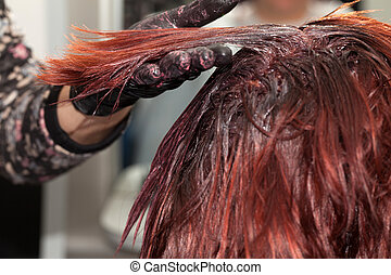 Hair Coloring - Hairdresser dyeing client's hair, closeup...