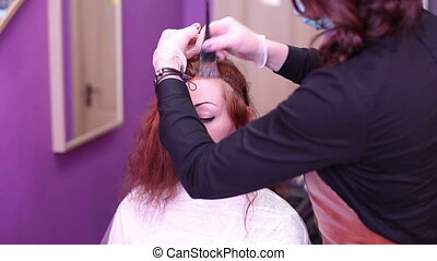 Hair coloring in red color - Woman in a beauty salon hair...