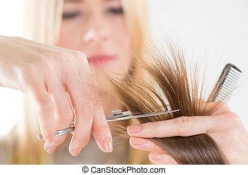 Hair Cutting - Hairdresser cut hair of a woman. Close-up.