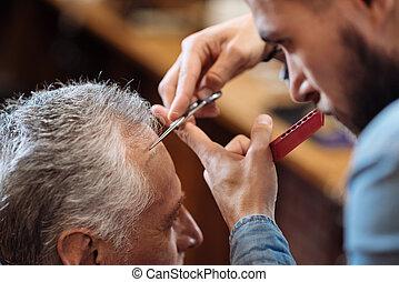 Hair dresser cutting bang of senior man